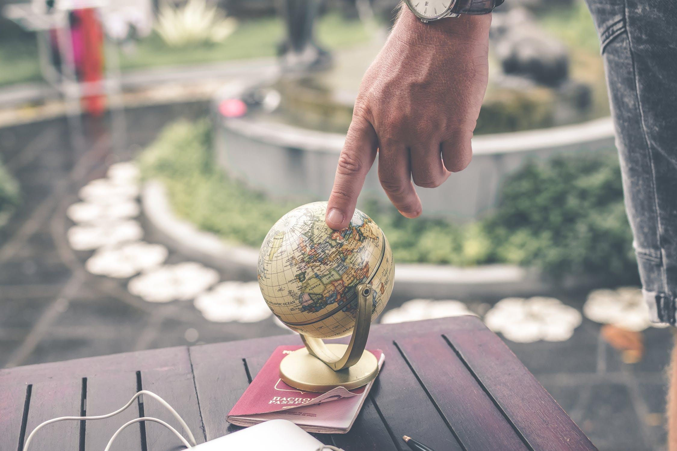 Mand peger med hånd på globus