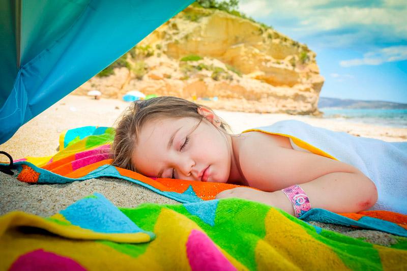 Pige sovende på stranden
